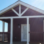 Picture shows optional 8 foot covered front porch with painted rails and crows feet trim gable.